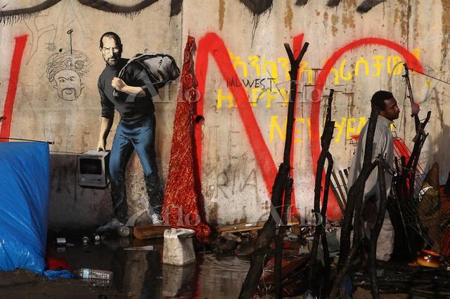 フランスの都市にあるカレーのシリア難民キャンプに出現したスティーブ・ジョブズの絵を描いたバンクシーの作品。シリア移民の父を持つ故ジョブズを難民風に描いたこと